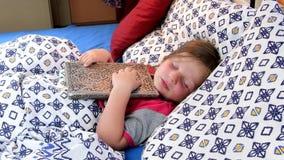 Liten flicka i underlag Flickatryies får sovande med en gammal faderdagbok Liten flicka med en gammal bok i säng bolts muttrar fö arkivfilmer