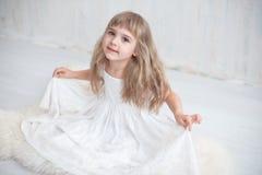 Liten flicka i vitt brett klänningsammanträde på golvet fotografering för bildbyråer