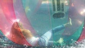 Liten flicka inom en stor uppblåsbar boll i vatten stock video