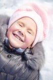 Liten flicka lägger på en snow royaltyfri bild
