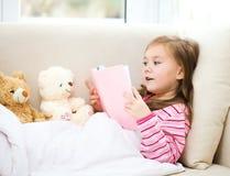 Liten flicka läser en bok för henne nallebjörnar royaltyfri foto