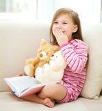 Liten flicka läser en bok för henne nallebjörnar arkivfoto