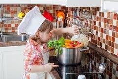 Liten flicka leker kocken Fotografering för Bildbyråer