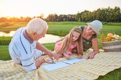 Liten flicka med att dra för morföräldrar arkivbild