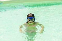 Liten flicka med att dyka exponeringsglas i en utomhus- pöl Royaltyfria Bilder
