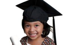 Liten flicka med avläggande av examenlocket Royaltyfri Bild