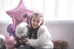 Liten flicka med ballonger som sitter på soffan royaltyfri foto
