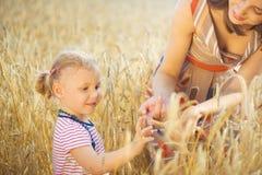 Liten flicka med barnmodern på kornvetefältet Arkivfoto