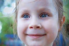 Liten flicka med blåa ögon som ler över Blured sommarbakgrund arkivbild