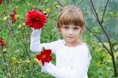 Liten flicka med blommor i trädgården fotografering för bildbyråer