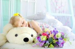 Liten flicka med blommor som omfamnar den stora nallebjörnen arkivbild