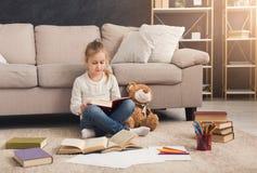Liten flicka med boken och hennes favorit- leksak hemma royaltyfri fotografi