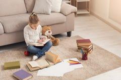 Liten flicka med boken och hennes favorit- leksak hemma arkivfoto
