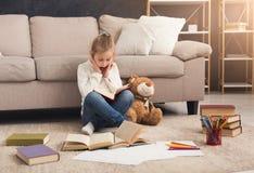Liten flicka med boken och hennes favorit- leksak hemma royaltyfri foto