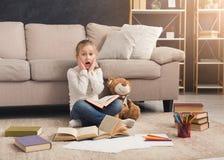 Liten flicka med boken och hennes favorit- leksak hemma royaltyfria bilder