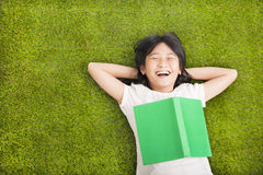 Liten flicka med boken och vila på gräset Fotografering för Bildbyråer