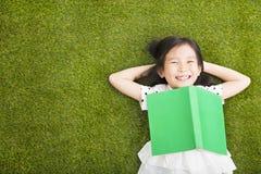 Liten flicka med boken och vila på gräset Arkivfoton