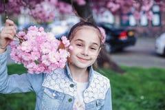 Liten flicka med brunt hår i det blåa grov bomullstvillomslaget som har gyckel i körsbärsröd trädgård för blomning på härlig vård arkivfoton