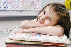 Liten flicka med bunten av böcker Royaltyfria Bilder