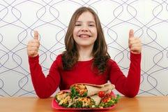 Liten flicka med burritos mexikansk mat och tummar upp arkivfoto