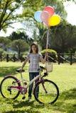 Liten flicka med cykeln och ballonger Arkivbild