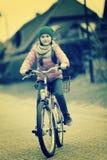 Liten flicka med cykeln på vägen. Retro bild Fotografering för Bildbyråer