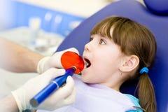 Liten flicka med den öppna munnen som mottar tand- fyllnads- uttorkningproc Arkivbilder