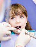 Liten flicka med den öppna munnen under borrandebehandling på hålan Arkivfoton