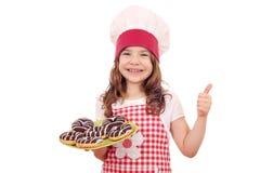 Liten flicka med den chokladdonuts och tummen upp Arkivfoton