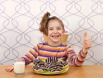 Liten flicka med den chokladdonuts och tummen upp Royaltyfri Bild