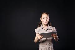 Liten flicka med den Digital minnestavlan på svart bakgrund arkivbilder
