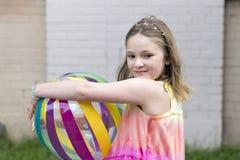 Liten flicka med den drömlika blicken som rymmer den mångfärgade strandbollen arkivfoto
