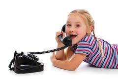 Liten flicka med den gammala retro telefonen. Arkivfoto