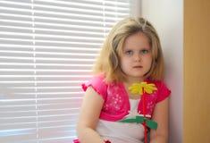 Liten flicka med den gula blomman Arkivfoton