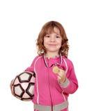 Liten flicka med den guld- medalj- och fotbollbollen royaltyfria bilder