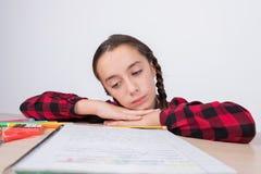 Liten flicka med den ledsna blicken som ser arbetsanteckningsboken på skola fotografering för bildbyråer