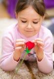 Liten flicka med den röda rosen Royaltyfri Bild