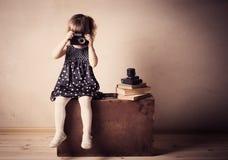 Liten flicka med den retro kameran på resväskan Arkivbilder