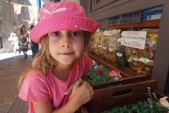 Liten flicka med den rosa hatten framme av en livsmedelsbutik, San Marino royaltyfri foto