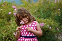 Liten flicka med den rosa rosen royaltyfri foto