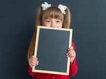 Liten flicka med den små blackboarden Royaltyfria Bilder