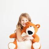 Liten flicka med den stora nallebjörnen som har att skratta för gyckel att isoleras på Royaltyfria Bilder
