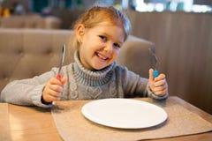 Liten flicka med den tomma plattan i restaurang royaltyfria foton