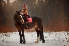 Liten flicka med den utomhus- ståenden för häst på vårdagen royaltyfria foton