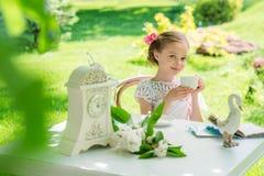 Liten flicka med den utomhus- vita koppen Fotografering för Bildbyråer