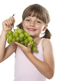 Liten flicka med druvor Arkivbild