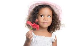Liten flicka med en afro frisyr som rymmer en röd blomma Royaltyfri Foto