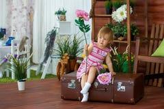 Liten flicka med en blomma på en resväska royaltyfria bilder