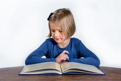Liten flicka med en bok på en vit bakgrund Arkivbild