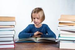 Liten flicka med en bok på en vit bakgrund Royaltyfria Bilder